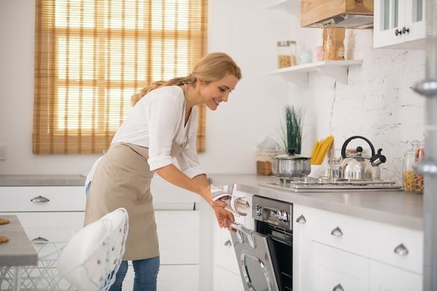Gospodyni w fartuchu otwierająca piekarnik w kuchni