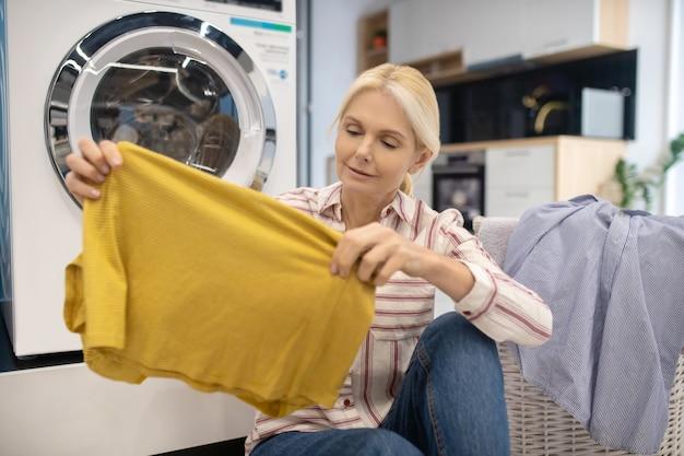 Gospodyni w pasiastej koszuli siedzi w pobliżu pralki i trzyma w rękach czyste ubrania