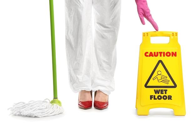 Gospodyni w stroju ochronnym, z mopem i znakiem ostrzegawczym na białym tle