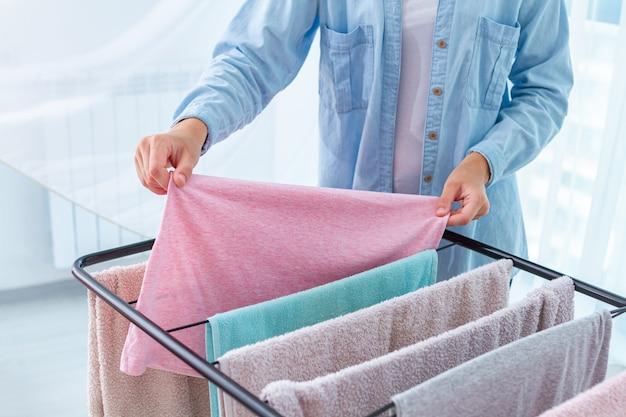 Gospodyni wisi mokre pranie na suszarce