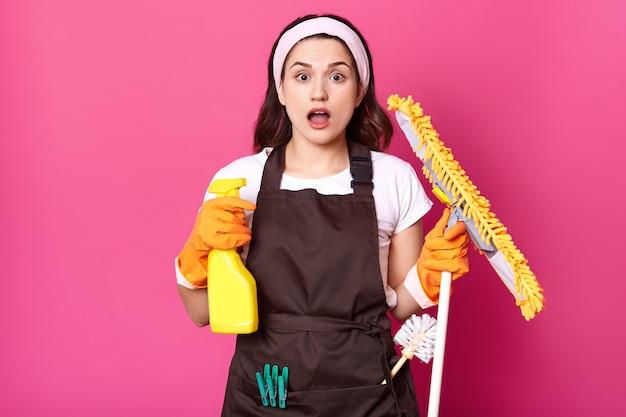 Gospodyni wpadająca w panikę, ponieważ ma tak wiele rzeczy do czyszczenia, stoi z otwartymi ustami, trzyma spray detergentu i żółty mop w rękach w pomarańczowych rękawiczkach, zszokowana dziewczyna na różowej ścianie studia.