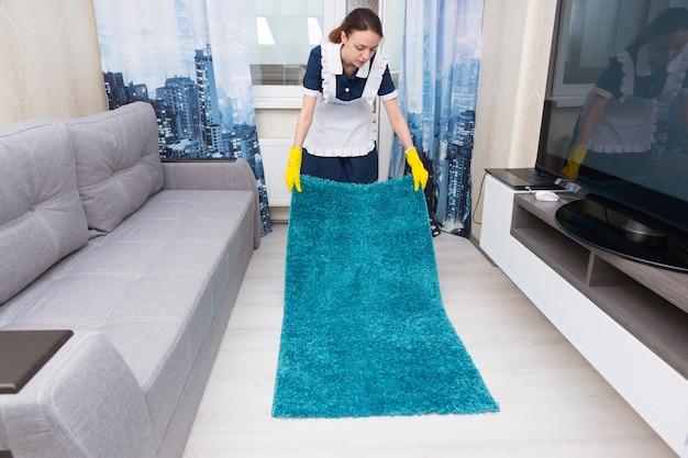 Gospodyni wymienia i umieszcza dywan na białej, wyłożonej kafelkami podłodze w pokoju rozrywki lub apartamencie hotelowym
