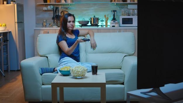 Gospodyni zmienia kanały telewizyjne siedząc na kanapie w salonie. znudzona, sama w domu późno w nocy kobieta relaks przed telewizorem leżąc na wygodnej kanapie trzymając pilota w poszukiwaniu filmu komediowego.