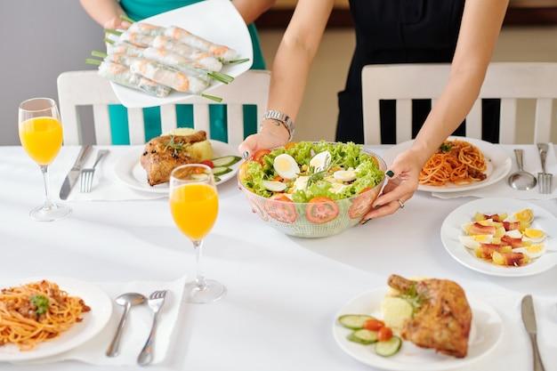 Gospodynie domowe kładą naczynia na stole podczas przyjęcia w domu