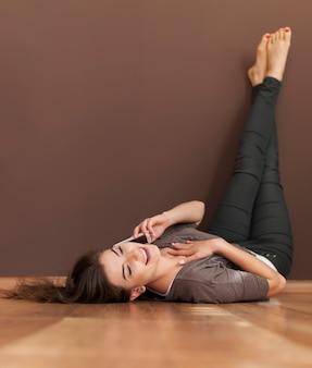 Gossip girl relaks na podłodze z telefonem komórkowym