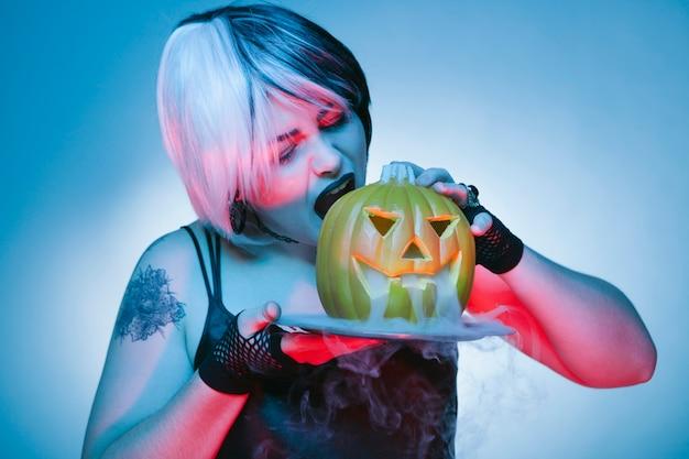 Goth kobieta o kęs palenia dyni halloween
