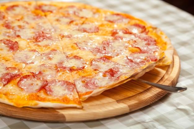 Gotowa cienka pyszna pizza na stole w kawiarni. gotowanie pizzy w pizzerii.
