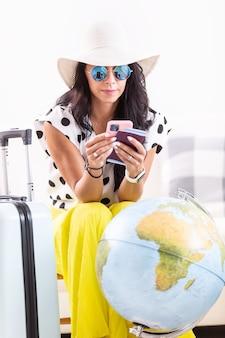 Gotowa do lotu pani kontroluje swoje dokumenty podróżne w domu z bagażem i kulą ziemską przed sobą.
