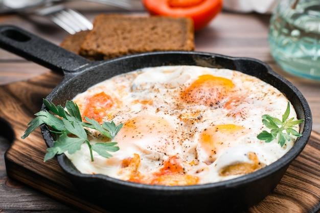 Gotowa do spożycia shakshuka ze smażonych jajek z pomidorami i natką pietruszki na patelni na drewnianym stole