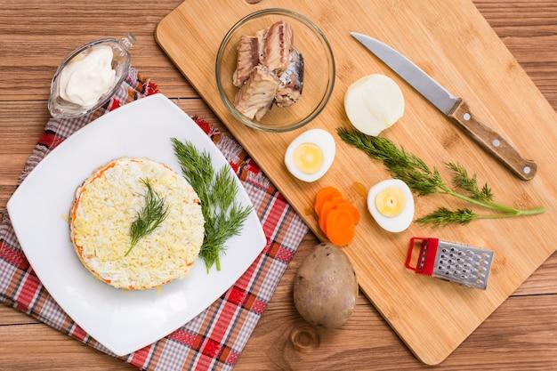 Gotowa sałatka mamoza i składniki do jej przygotowania na stole, widok z góry