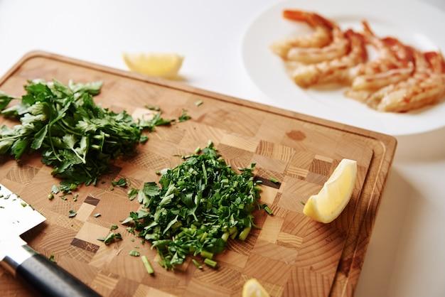 Gotować obiad. posiekana pietruszka na desce do krojenia i świeże krewetki na stole