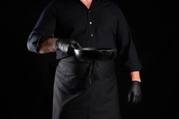 Gotować w czarnych rękawiczkach mundurowych i lateksowych trzymając patelnię