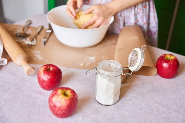 Gotować w domu. kobieta ugniata ciasto na szarlotkę na kuchennym stole z jabłkami, cukier - widok z boku