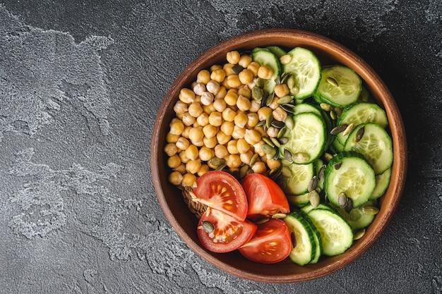 Gotowana ciecierzyca z pokrojonymi pomidorami i ogórkami w glinianym garnku widok z góry