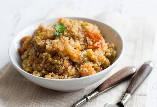 Gotowana komosa ryżowa z warzywami i krewetkami w misce z bliska
