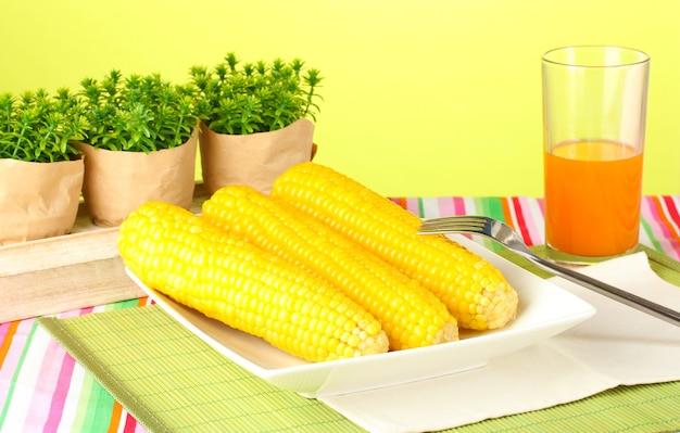 Gotowana kukurydza i sok na zielonym tle