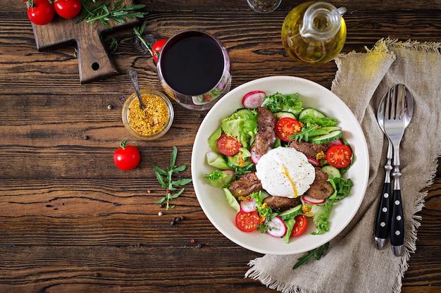Gotowana na ciepło sałatka z wątróbki drobiowej, rzodkiewki, ogórka, pomidorów i jajek. zdrowe jedzenie. menu dietetyczne. widok z góry. leżał płasko