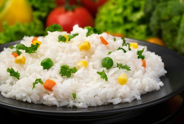 Gotowana owsianka ryżowa podawana z ziołami i warzywami na czarnym talerzu