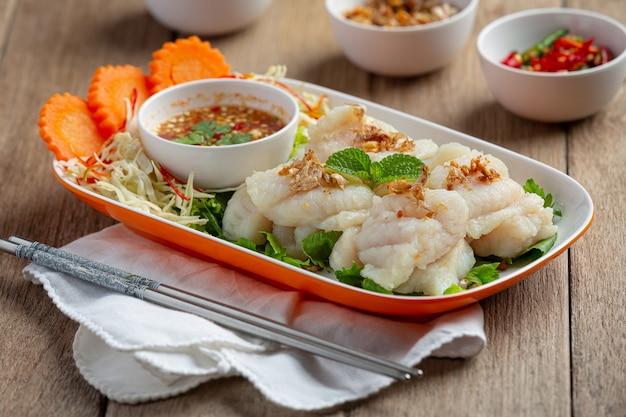 Gotowana ryba dolly z pikantnym sosem z owoców morza.