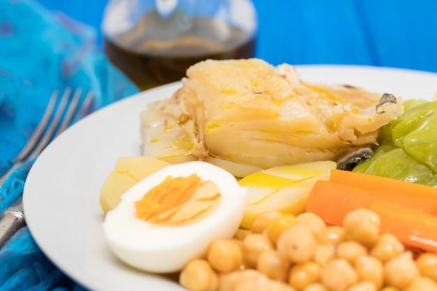 Gotowana ryba dorsz z ziemniakami, marchewką, kapustą, ciecierzycą i jajkiem na białym talerzu