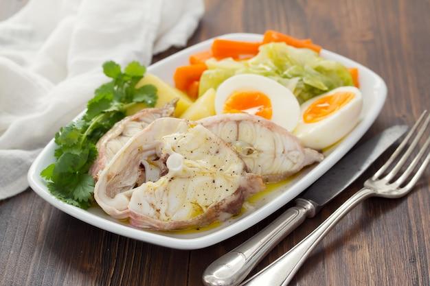 Gotowana ryba z gotowanym ziemniakiem, marchewką, kapustą i jajkiem na białym talerzu