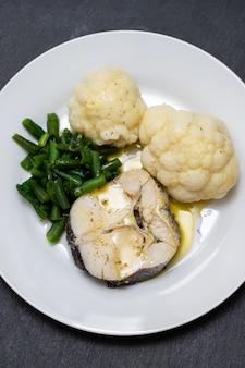 Gotowana ryba z gotowanymi warzywami na bielu talerzu