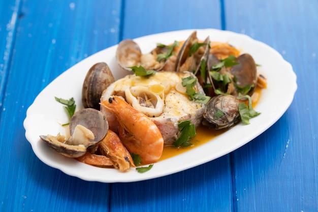 Gotowana ryba z owocami morza na naczyniu