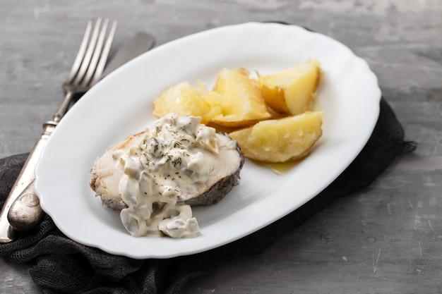 Gotowana ryba z sosem tatarskim i gotowanym ziemniakiem na białym talerzu na ceramicznym tle