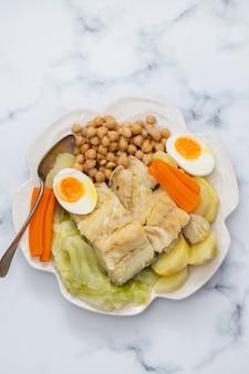 Gotowana ryba z warzywami i gotowanym jajkiem na białym talerzu
