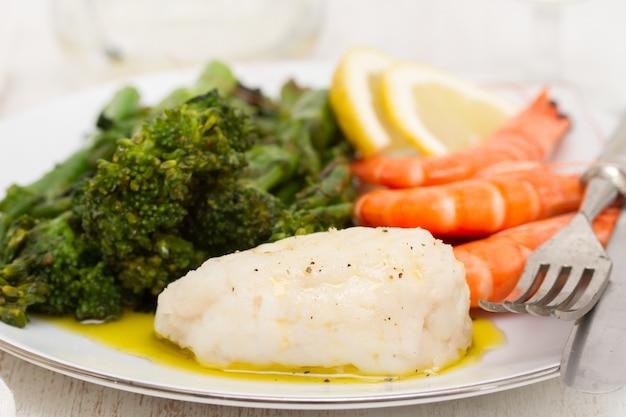 Gotowana ryba z zieleniami i krewetkami na białym naczyniu