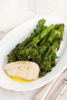Gotowana ryba z zieleniami i oliwa z oliwek na białym naczyniu na drewnianej powierzchni