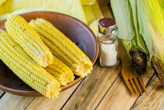 Gotowana słodka młoda kukurydza na talerzu i sól