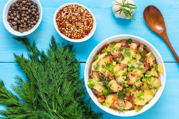 Gotowana tartiflette z boczkiem i ziołami na drewnianym niebieskim stole. widok z góry.