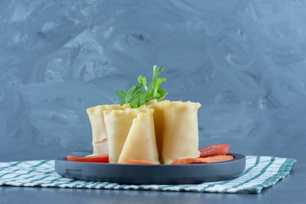 Gotowane bułki i warzywa na ciemnej desce.