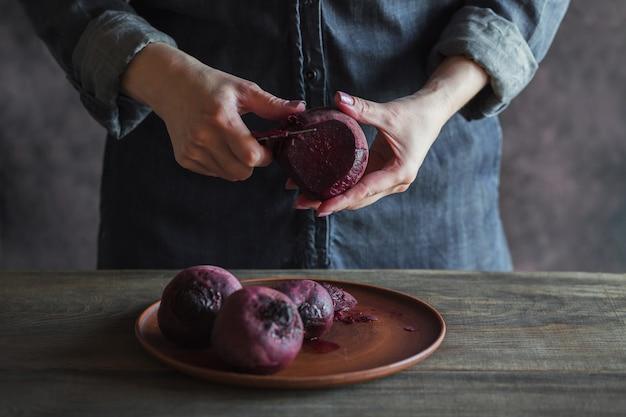 Gotowane buraki na glinianym talerzu. kobieta clianing buraków nożem. koncepcja zdrowej żywności.