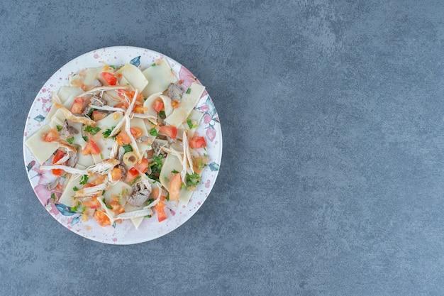 Gotowane ciasto z posiekanymi warzywami na kolorowym talerzu.