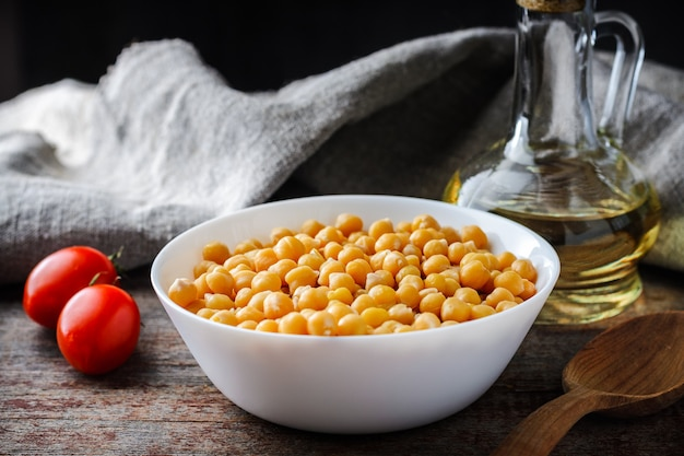 Gotowane ciecierzycy w talerz, pomidory i oliwa z oliwek na drewnianym stole