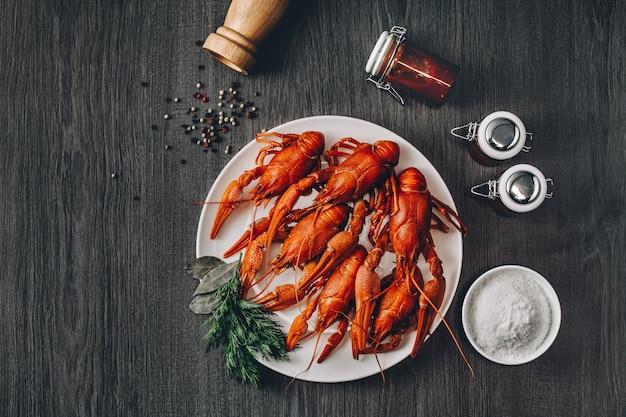 Gotowane duże czerwone świeże raki w białym talerzu z zielonymi ziołami