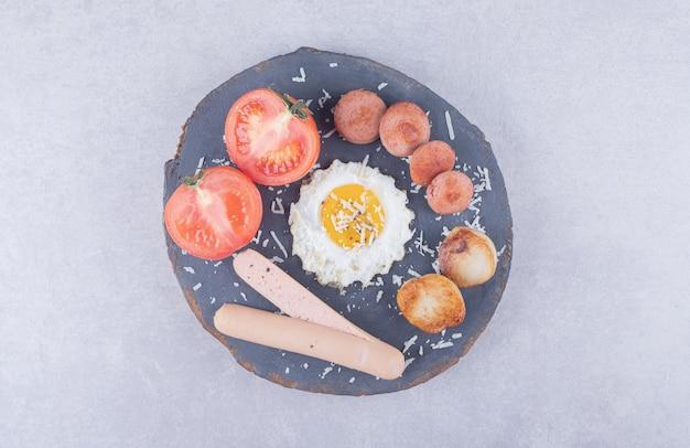 Gotowane i smażone kiełbaski z jajkiem na kawałku drewna.