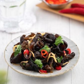 Gotowane jadalne drzewo czarny grzyb, ucho drewna w talerzu na białej powierzchni stołu.