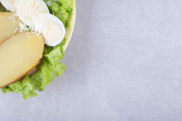 Gotowane jajka i ziemniaki na żółtym talerzu.