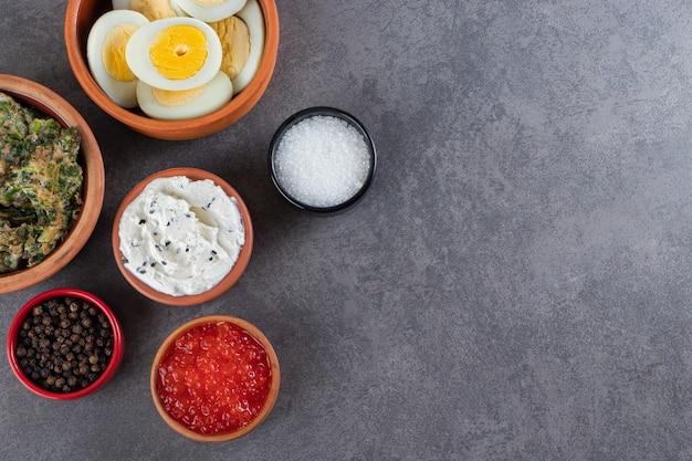 Gotowane jajka w plasterkach z przyprawami umieszczone na kamiennym tle.