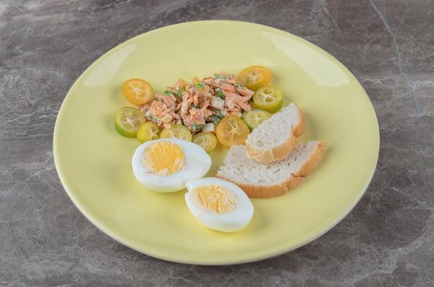 Gotowane jajka, warzywa i chleb na żółtym talerzu.