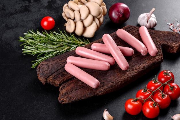 Gotowane kiełbaski na drewnianej desce do krojenia. niezdrowe jedzenie
