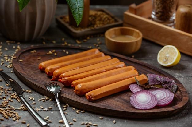 Gotowane kiełbaski na drewnianym talerzu z plasterkami czerwonej cebuli