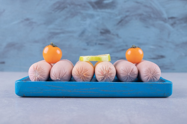Gotowane kiełbaski ozdobione cytryną i pomidorami na niebieskim talerzu.