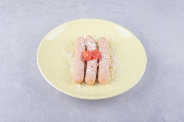 Gotowane kiełbaski ozdobione pomidorami na żółtym talerzu.