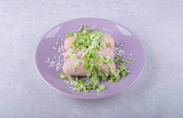 Gotowane kiełbaski ozdobione sałatą na fioletowym talerzu.