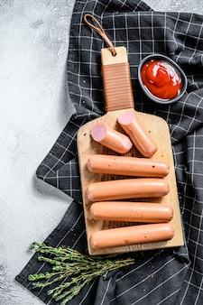 Gotowane klasyczne kiełbaski wieprzowe na desce do krojenia z rozmarynem i przyprawami.