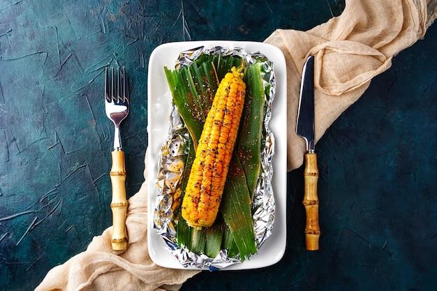 Gotowane kolby kukurydzy na otwartym ogniu pieczona kukurydza z przyprawami płasko leżące widok z góry grillowane warzywa...